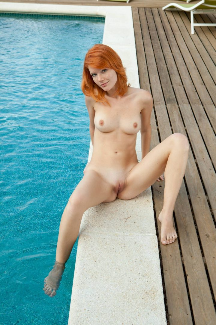 red head with her legs open by the pool.jpg